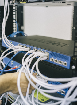 Picture of a hand plugging a network cable into a large networking hub, link to Remote Support page on of the Digital Services provided by encoreservices.co.za.